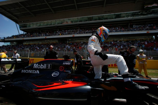 Fernando Alonso climbs from his car on the grid.